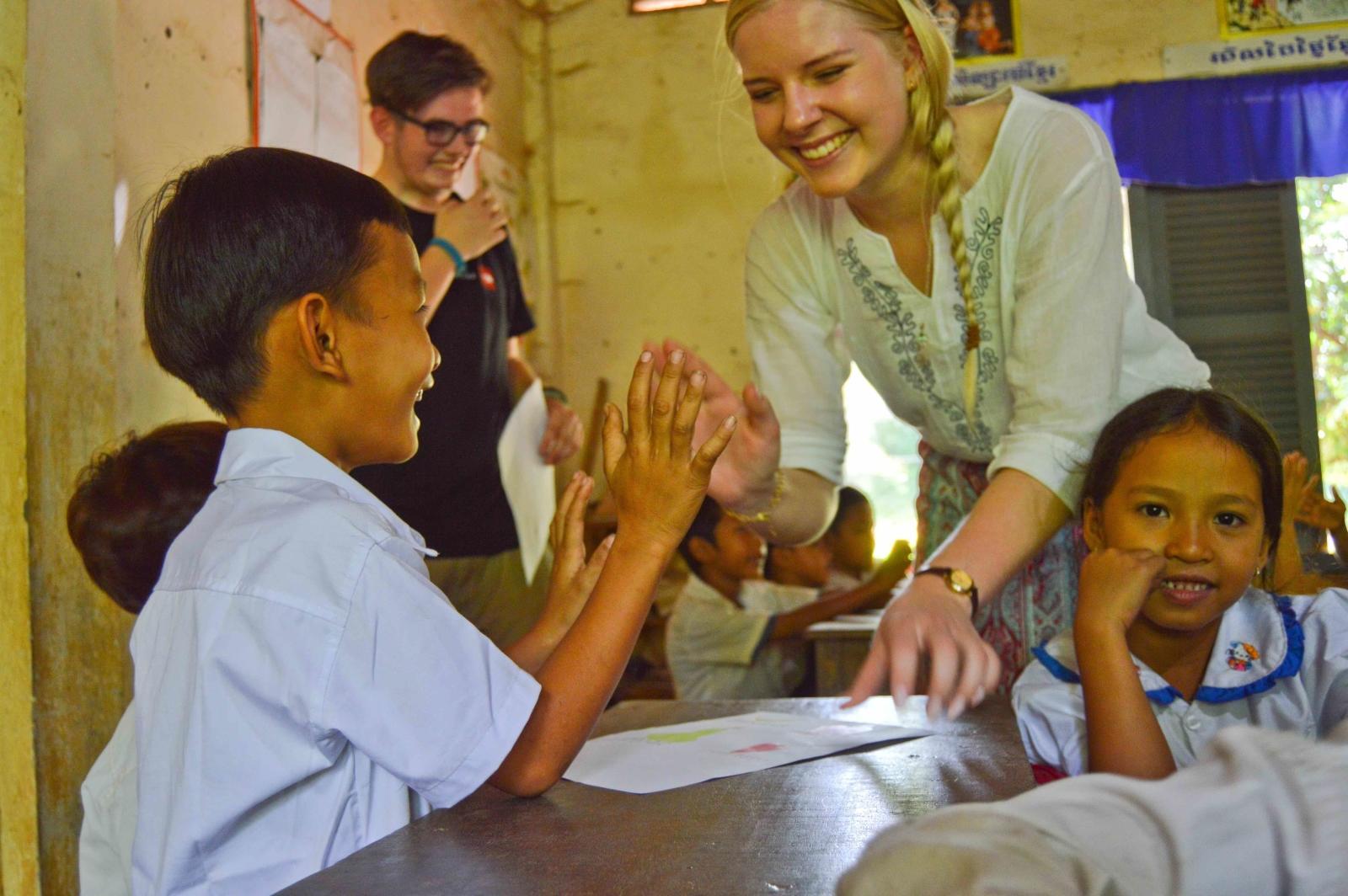 Voluntaria jugando con niños en Camboya.
